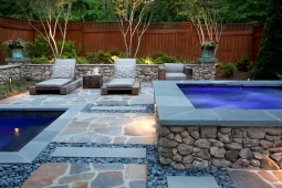 Beautifully designed, this backyard features several stone accents.