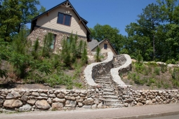 A stonework walkway beautifully accents the landscaping outside this custom home.