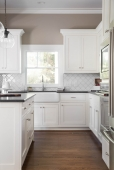 White cabinets, clean modern tile, farmhouse sink, and honed granite makes this kitchen a showstopper!