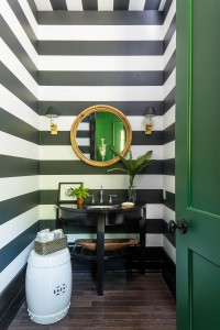 Designed by Bill Ingram, the bold striped wallpaper create drama in the powder room.