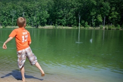 A neighborhood boy skips rocks at Spoonwood Lake.