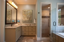 This luxurious bathroom includes a spacious shower, ornate tub, and marble countertops.